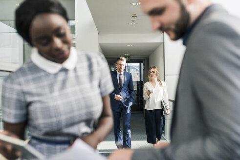 Business people talking on office floor - UUF12437
