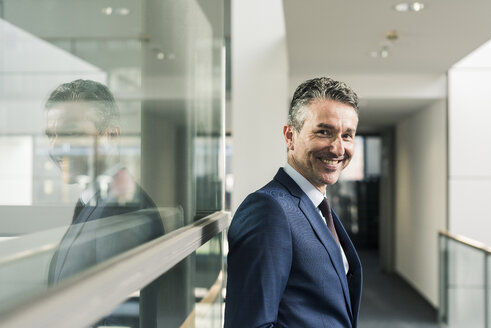 Portrait of smiling businessman on office floor - UUF12440