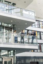 Business people talking on office floor - UUF12446