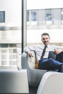 Portrait of smiling businessman sitting in lounge with tablet - UUF12452