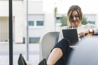 Smiling businesswoman sitting in lounge with tablet - UUF12458