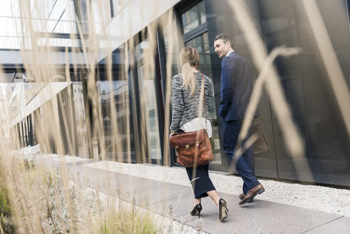 Businessman and woman walking outside office building - UUF12461
