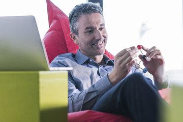 Smiling man sitting in beanbag holding molecule model - UUF12464