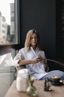 Young woman sitting in cafe using smartphone - GUSF00197