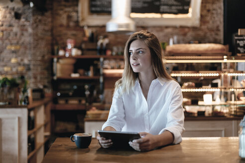 Blond woman sitting in cafe, using tablet, thinking - GUSF00200