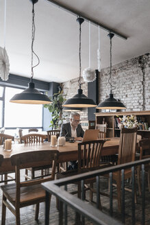 Businessman sitting in cafe, using laptop - GUSF00233