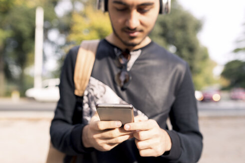 Young man with headphones and cell phone outdoors - FMOF00325