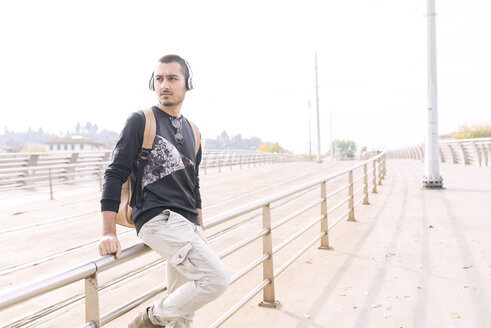 Young man with headphones and backpack at railing outdoors - FMOF00328