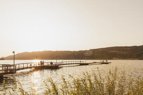 Germany, Bavaria, Allgaeu, Grosser Alpsee,  people on jetty at sunset - GWF05317