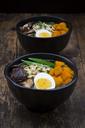 Ramen with noodles, egg, hokkaido pumpkin, mung sprout, shitake mushroom in bowl, chopsticks - LVF06452