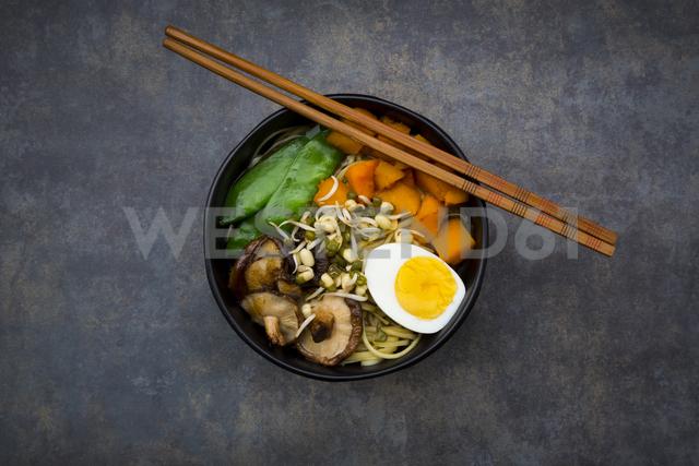 Ramen with noodles, egg, hokkaido pumpkin, mung sprout, shitake mushroom in bowl, chopsticks - LVF06455