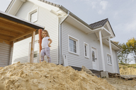 Happy blond girl standing on heap of sand near construction site of a detached one-family house - KMKF00065