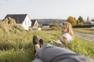 Portrait of little girl sitting on a meadow with a book looking at her mother - KMKF00074