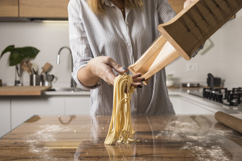 Woman preparing homemade pasta, row noodles, pasta harp - MAUF01264