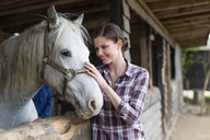 Smiling woman caring for a horse on a farm - SHKF00802