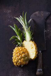 Sliced baby pineapple and old cleaver on rusty metal - CSF28562