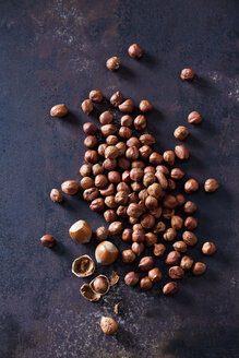 Whole and cracked hazelnuts on rusty metal - CSF28571