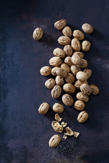 Whole and cracked walnuts on dark metal - CSF28574