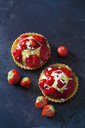 Two strawberry tartlets with custard and white chocolate shaving on dark ground - CSF28580