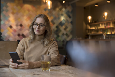 Portrait of businesswoman in restaurant using cell phone - SUF00343