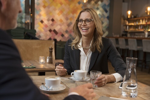 Portrait of laughing businesswoman having meeting in a restaurant - SUF00355