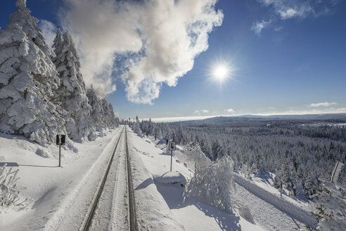 Germany, Saxony-Anhalt, Harz National Park, Brocken, rail tracks of Harz Narrow Gauge Railway in winter against the sun - PVCF01184
