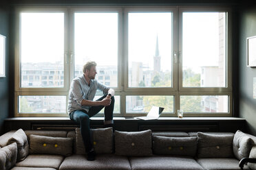 Businessman sitting at the window in lounge area of an office - JOSF02018