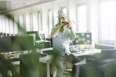 Businessman wearing VR glasses in office - JOSF02030