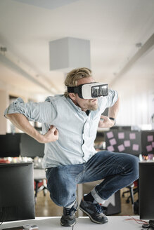 Businessman wearing VR glasses in office pretending to be a monkey - JOSF02033