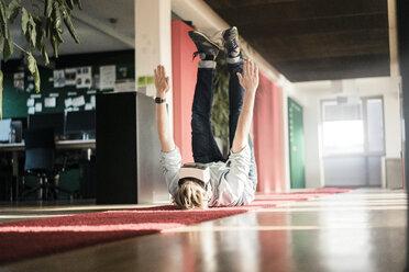 Businessman lying on carpet on the floor wearing VR glasses exercising - JOSF02036