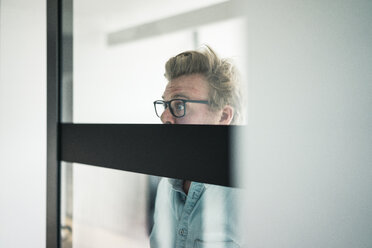Wide-eyed businessman behind glass pane in office - JOSF02039
