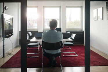 Businessman in conference room of an office with two laptops - JOSF02042