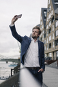 Businessman taking a cell phone selfie at the riverside - JOSF02051