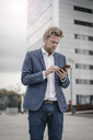 Businessman using cell phone in the city - JOSF02054