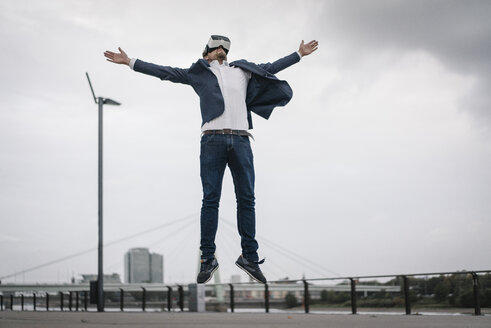 Businessman wearing VR glasses jumping in the city - JOSF02057