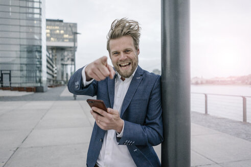 Portrait of happy businessman with cell phone in the city - JOSF02060