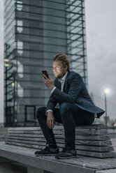 Businessman sitting on bench in the city holding cell phone - JOSF02072