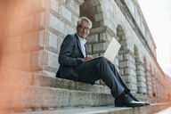 Senior businessman sitting on stairs, using laptop - GUSF00257