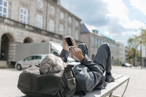 Senior businessman using smartphone, lying on bench in the city - GUSF00260