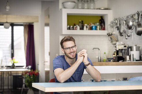Portrait of smiling young man sitting at kitchen table at home - PESF00751