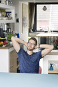 Portrait of smiling young man sitting at kitchen table at home - PESF00757