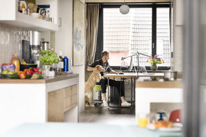 Man with dog working at desk at home - PESF00760