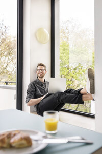 Happy man using laptop at the window at home - PESF00766