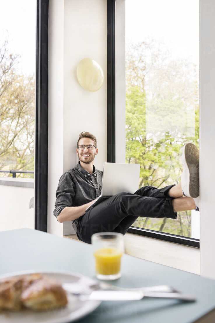 Happy man using laptop at the window at home - PESF00766 - Peter Scholl/Westend61
