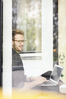 Portrait of smiling man using laptop at the window - PESF00769