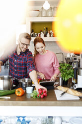 Happy young couple with tablet cooking together in kitchen - PESF00781