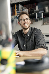 Portrait of smiling man working at desk at home - PESF00787