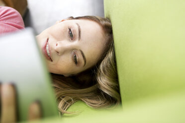 Portrait of smiling woman lying on the couch using tablet - PESF00799
