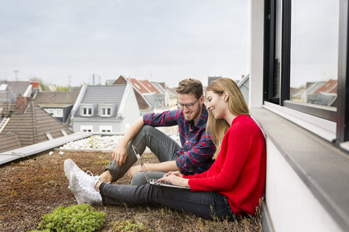 Smiling young couple sitting on roof of city apartment using laptop - PESF00808