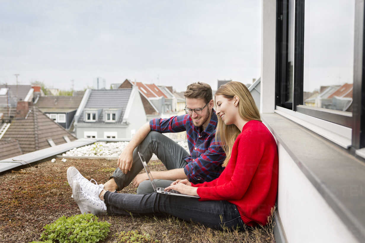 Smiling young couple sitting on roof of city apartment using laptop - PESF00808 - Peter Scholl/Westend61